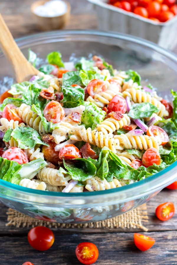 A glass Pyrex bowl full of a BLT pasta salad being mixed together with a wooden spoon.
