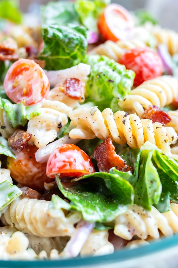 Fusilli pasta, Romaine lettuce, bacon pieces, and cherry tomatoes in a Ranch dressing pasta salad sauce in a clear bowl.