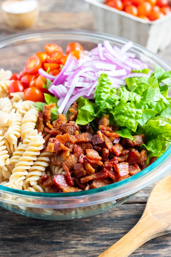 A pasta salad in a clear glass bowl with bacon, lettuce, and tomatoes.