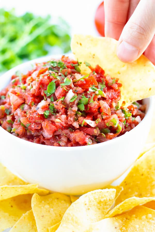 A thick and chunky salsa in a white bowl and a hand dipping a tortilla chip into it.