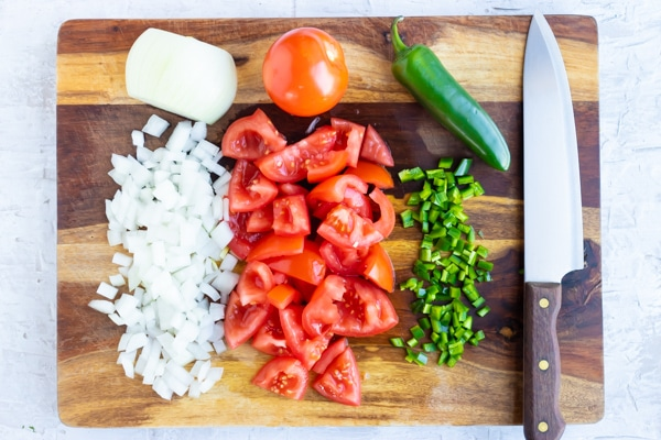Diced onion, fresh tomatoes, and jalapenos that are chopped on a wooden cutting board.