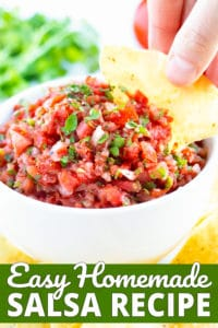 A thick and chunky salsa recipe in a white bowl and a hand dipping a tortilla chip into it.