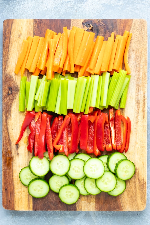 Cucumbers, bell peppers, celery, and carrots that are cut to be served with hummus.