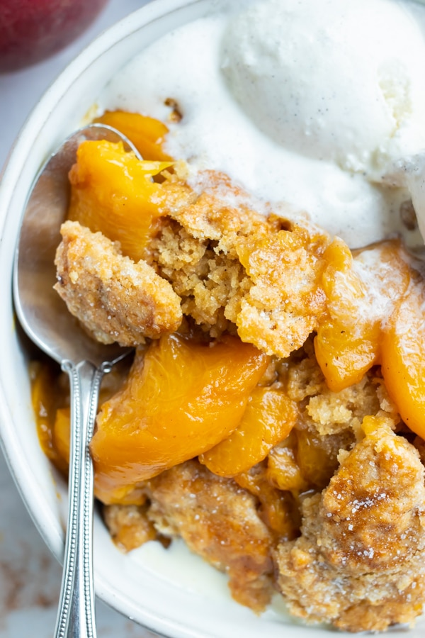 The best peach cobbler recipe is in a white bowl and served with vanilla ice cream.
