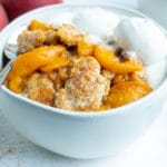 A gluten-free peach cobbler in a white bowl is placed on the counter.