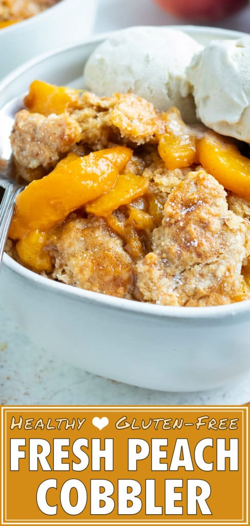 A big bowl of healthy, homemade cobbler made with tender peaches is topped with two scoops of vanilla ice-cream.