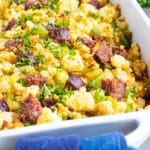 A white baking dish full of homemade cornbread dressing with sausage.