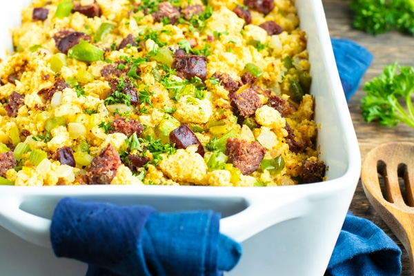 A blue towel on a wooden backdrop with a homemade cornbread dressing recipe.