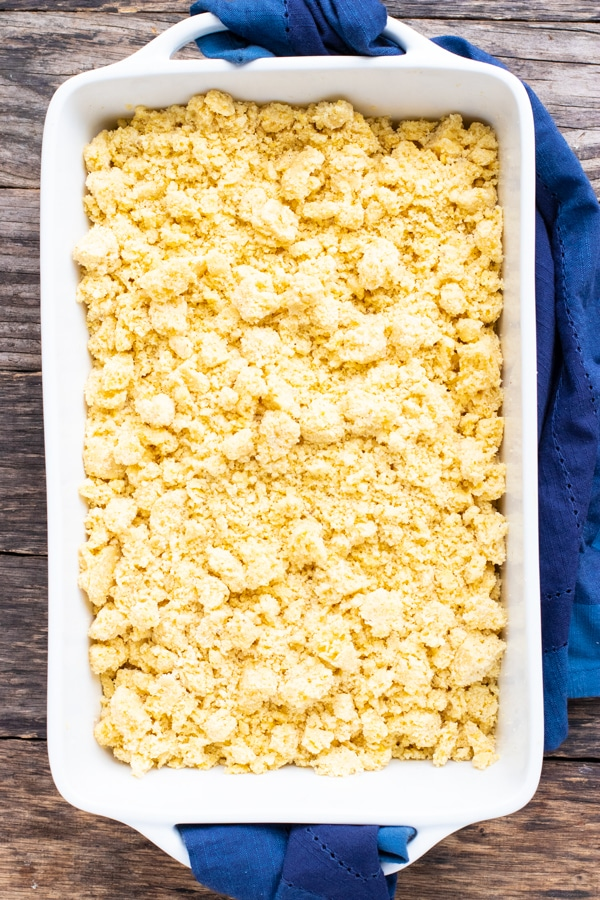 Gluten-free cornbread dressing mix in a white casserole dish with a blue dish towel.