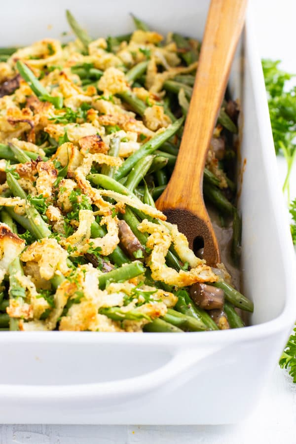 Green bean casserole recipe in a white baking dish with a wooden spoon.