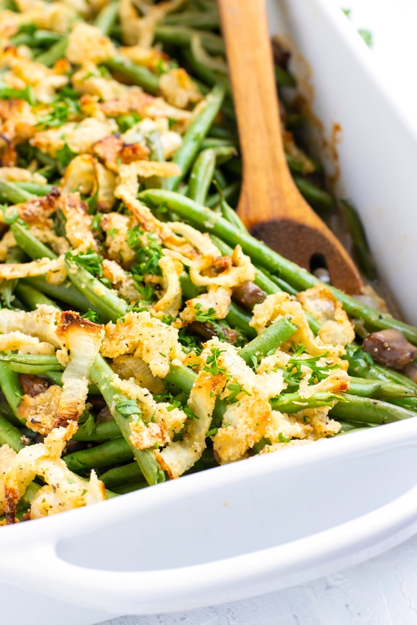 Green bean casserole recipe with baked onions and fresh green beans in a white 9 x 13 inch pan.
