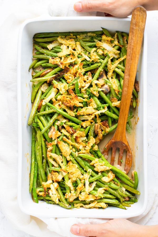 Hands holding a green bean casserole from scratch on a white background.