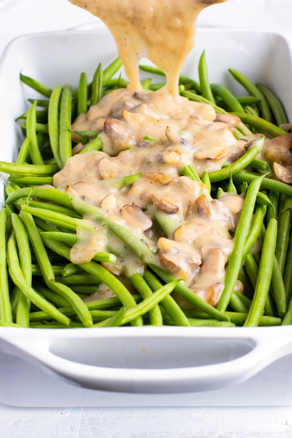 Gluten-free and vegan cream of mushroom soup being poured over fresh green beans in a white baking dish.