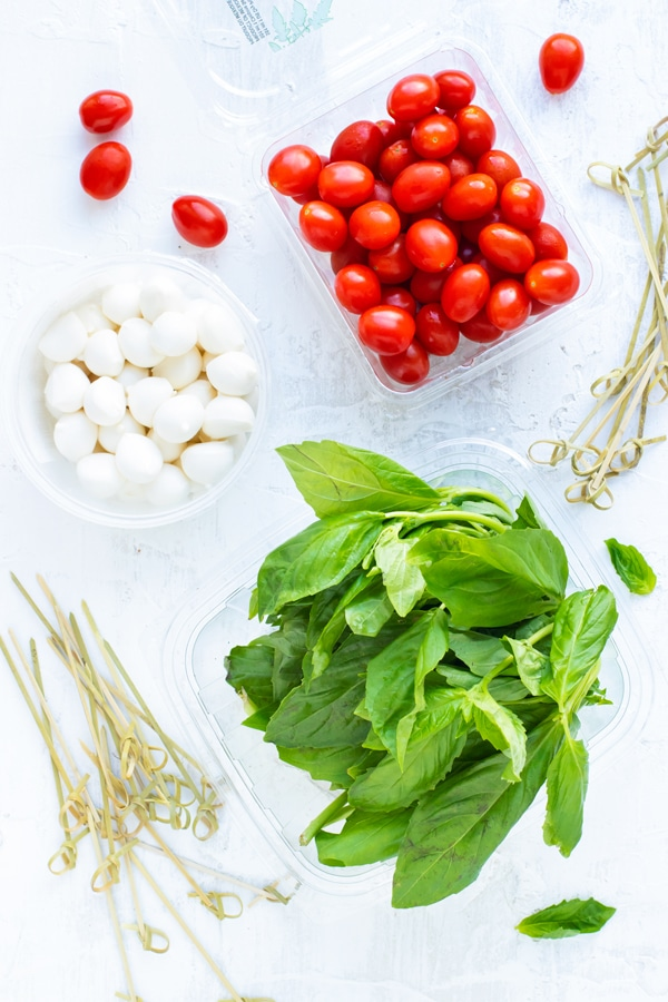 A pint full of cherry tomatoes, mozzarella pearls, and fresh basil leaves as the ingredients for caprese skewers.