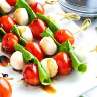 Caprese salad skewers on a white serving platter with a clear bowl full of balsamic glaze.
