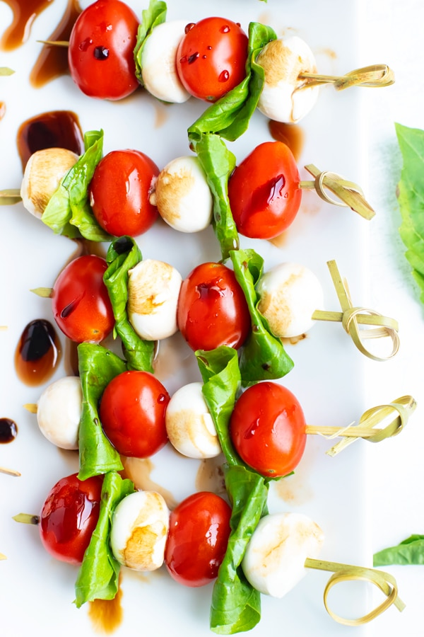 Caprese skewers on a white plate with a drizzle of balsamic glaze.