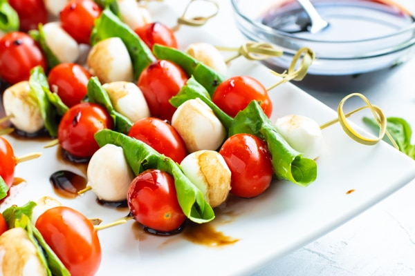 Caprese salad on wooden skewers with balsamic glaze in the background.