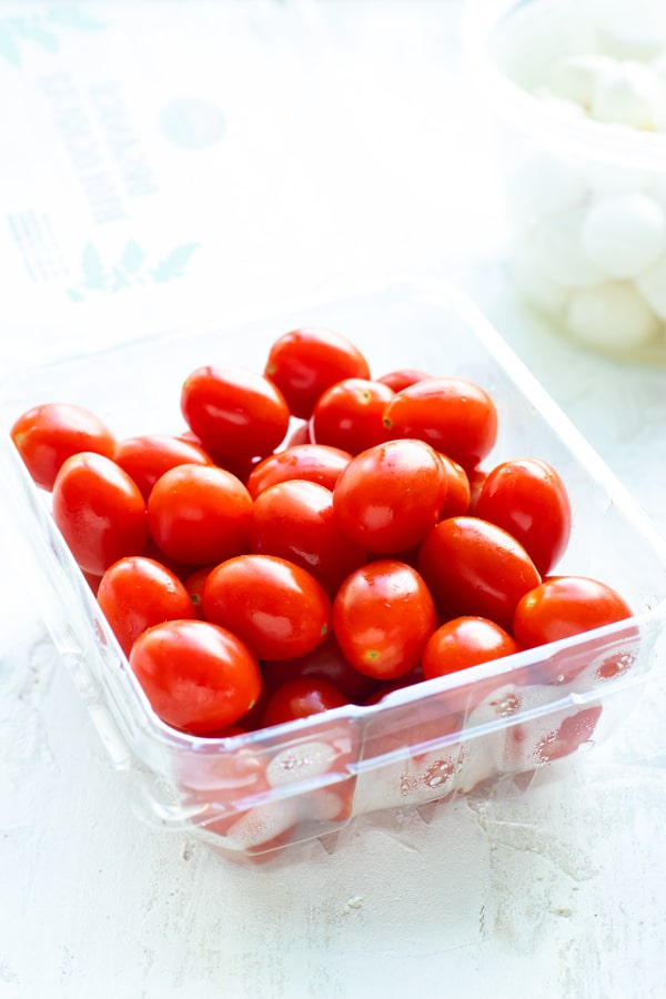 A pint full of cherry tomatoes with mozzarella in the background.