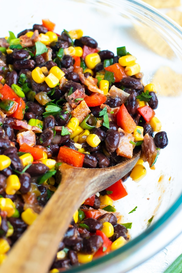 Black bean and corn salsa recipe in a clear Pyrex bowl with bacon.