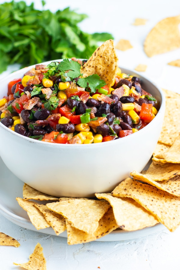 Black bean dip recipe with corn, green onions, and salsa in a white bowl with corn tortilla chips.