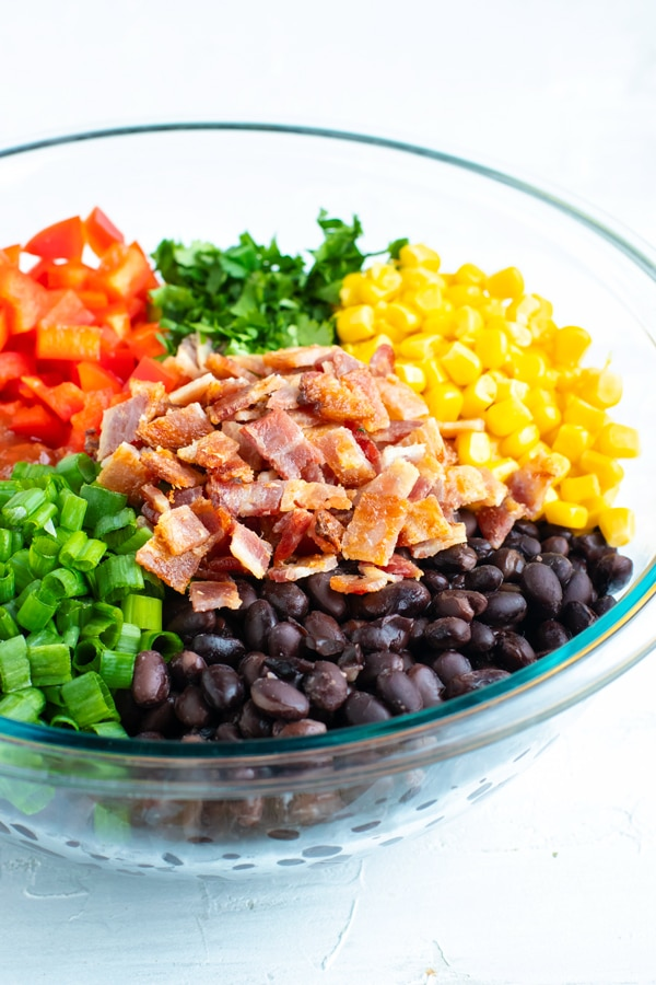 Ingredients for a black bean and corn salsa recipe in a clear Pyrex bowl.