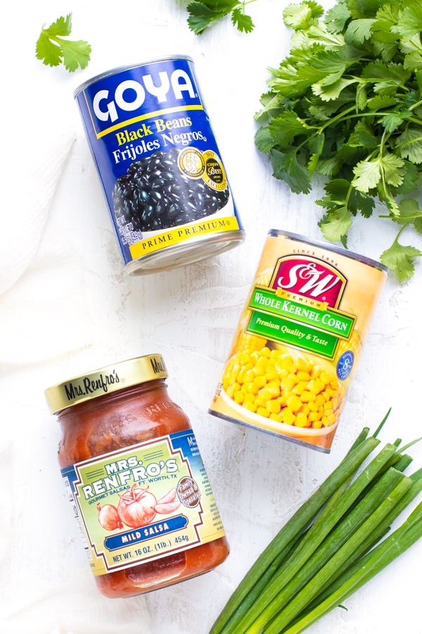 A can of black beans, a can of kernel corn, mild salsa, cilantro, and green onions on a white background.