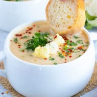 A piece of bread being dunked into a bowl full of vegan cauliflower soup.