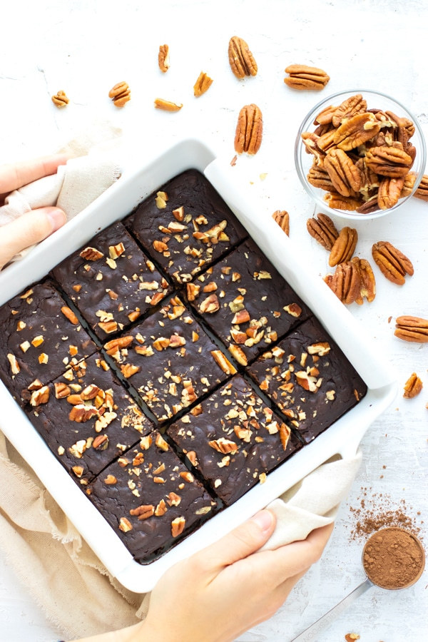 A white baking dish full of black bean brownies next to a bowl full of pecans.