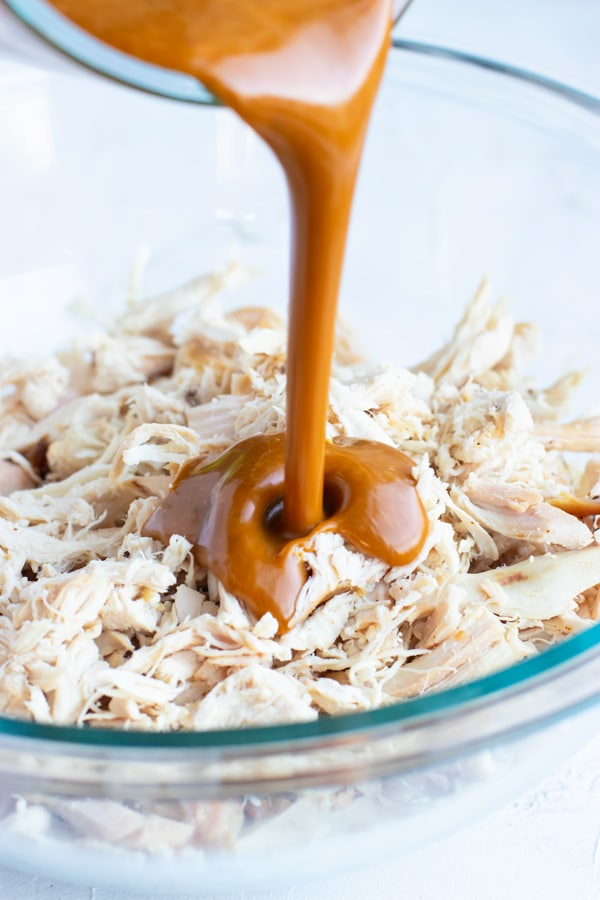Asian peanut butter sauce being poured into a clear bowl full of shredded rotisserie chicken.