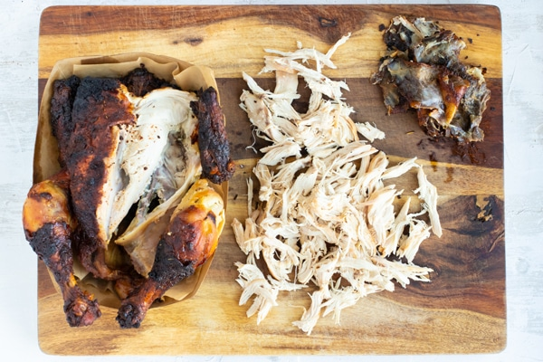 A rotisserie chicken that has been shredded on a wooden cutting board for a lettuce wraps recipe.