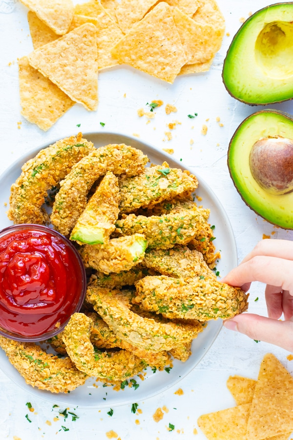 A hand that is grabbing an avocado fry from a white plate full of avocado fries with tortilla chips surrounding it.