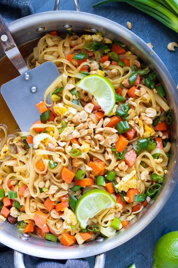 A large skillet full of a vegetarian Pad Thai recipe with limes.