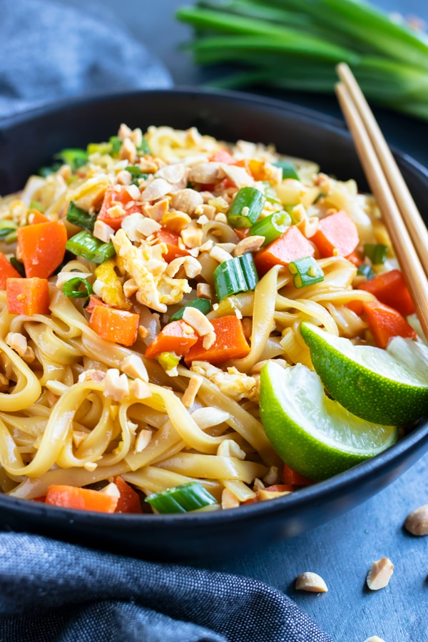 A healthy, gluten-free rice noodle stir-fry dish with chopsticks.