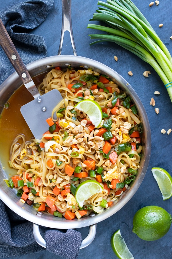 A large skillet full of a vegetarian Pad Thai recipe with limes and green onions on the side.