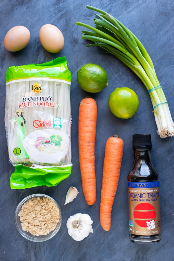 Rice noodles, carrots, lime, green onions, eggs, soy sauce, brown sugar, and garlic as the recipe ingredients.