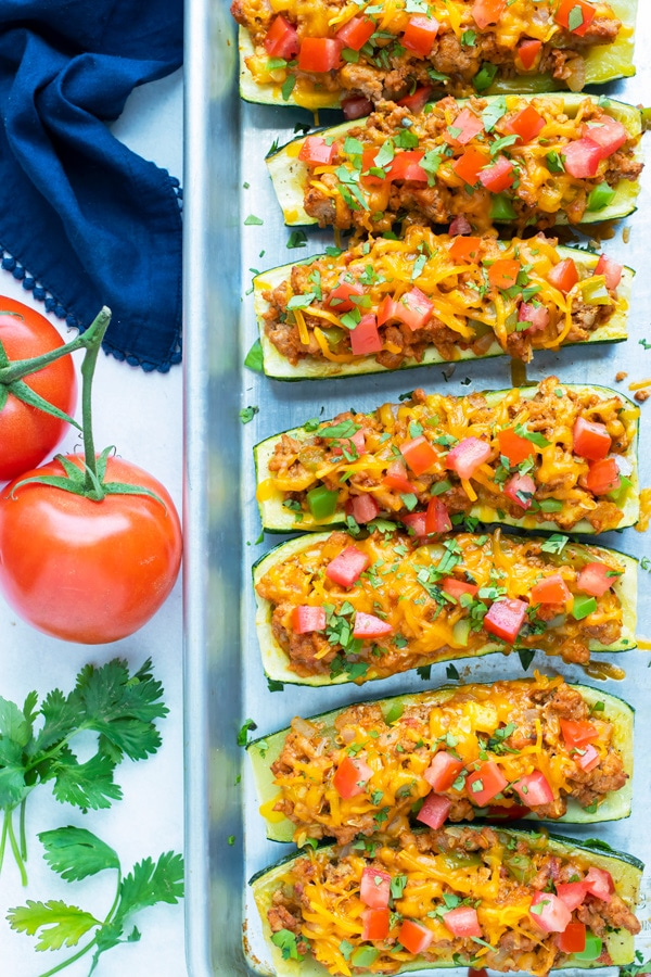 A row of zucchini boats stuffed with ground beef and taco ingredients.