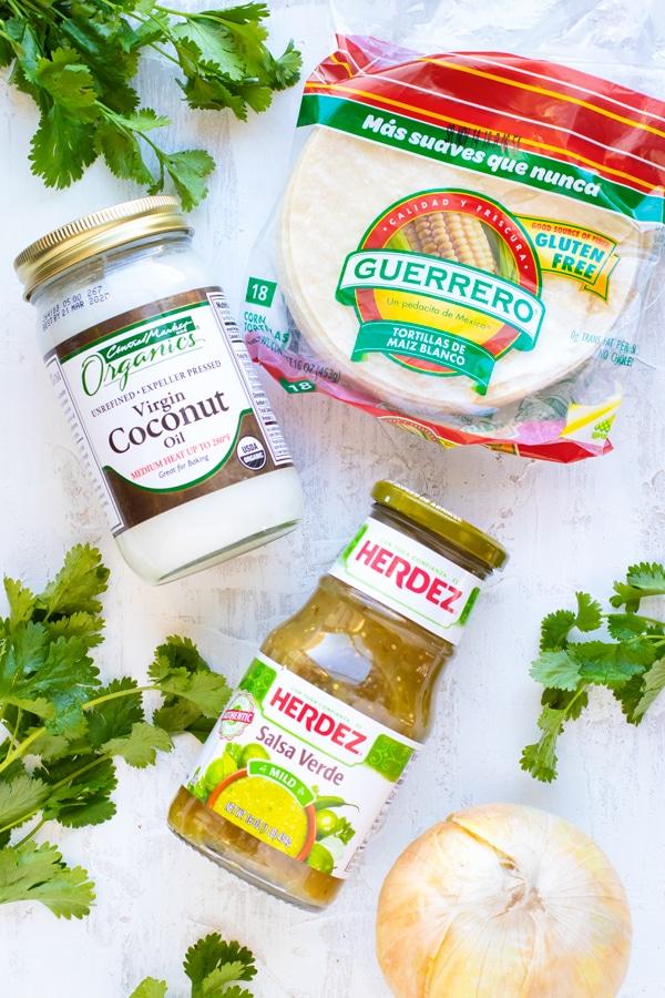 Corn tortillas, coconut oil, and salsa verde as the ingredients for chicken enchiladas verdes.