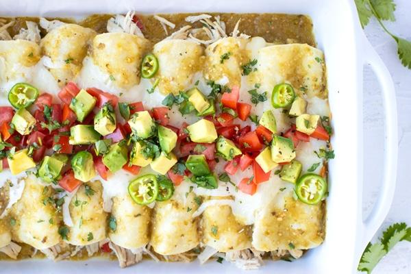 Chicken enchiladas recipe with salsa verde, chicken, and cheese in a white baking dish.