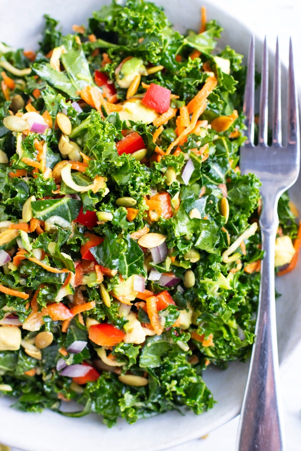 A large white bowl full of kale, avocado, bell pepper, carrots, and a lemon salad dressing.