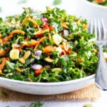 A healthy kale salad recipe with carrots, avocado, and a lemon salad dressing in a white bowl.