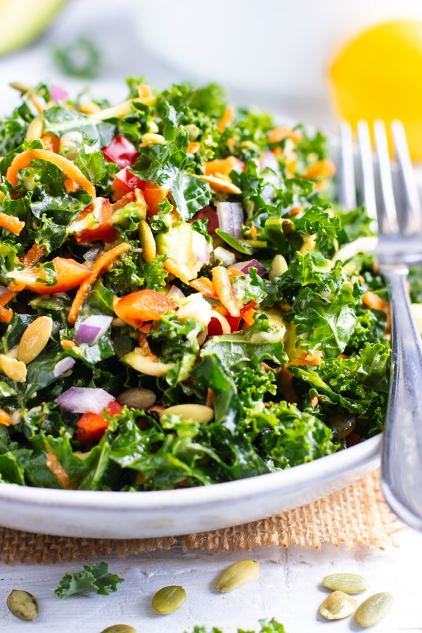 A massaged kale salad with avocado in a white bowl.