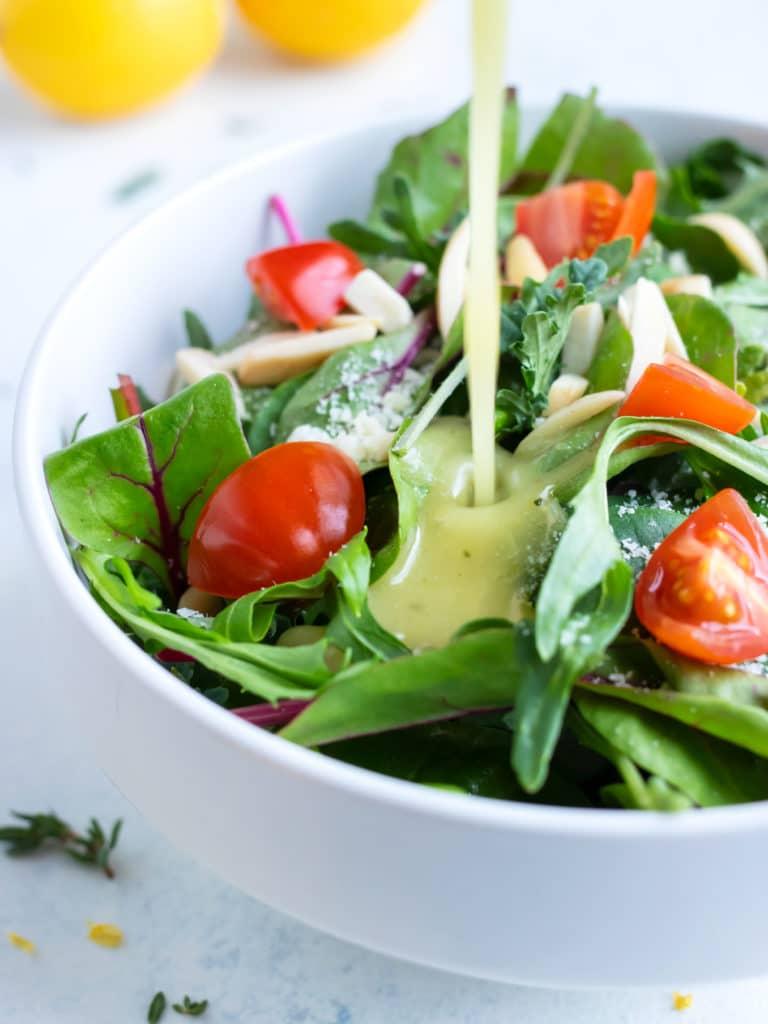 Lemon dressing is pour on a salad.