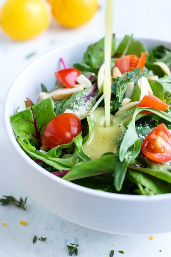 Lemon Vinaigrette is drizzled onto a healthy green salad.