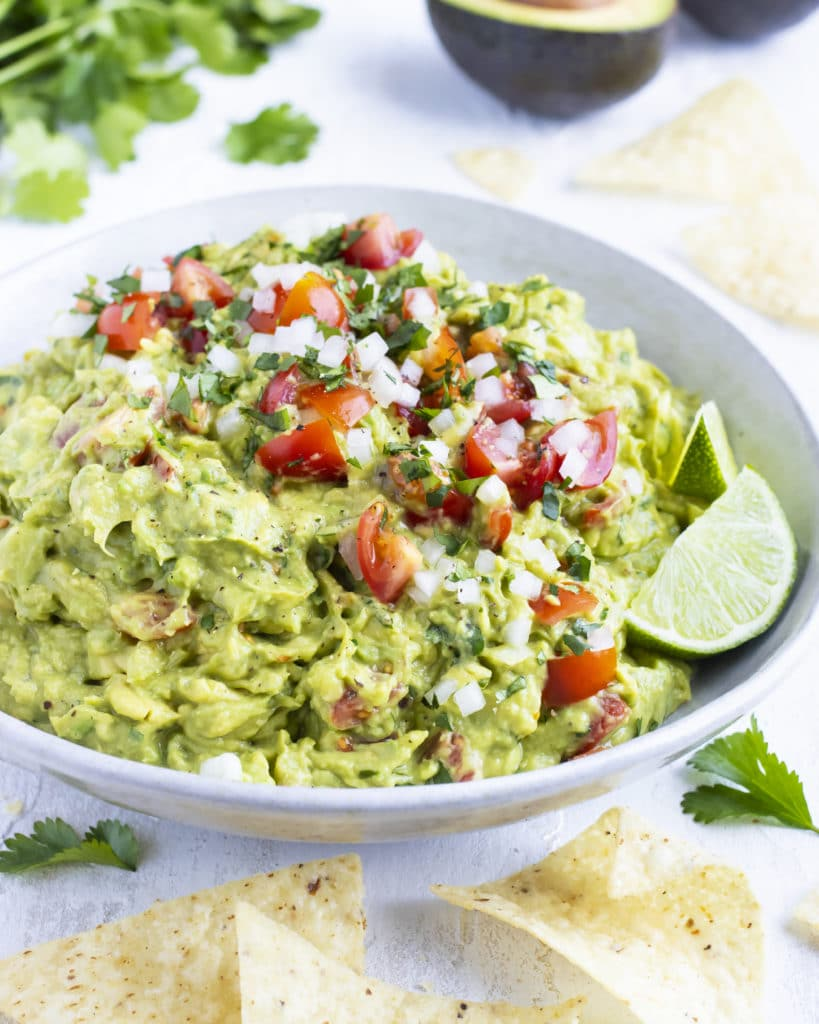 A party size serving bowl full of an easy homemade guacamole recipe with tortilla chips around it.