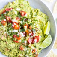 A white bowl full of a simple guacamole recipe with limes, tomatoes, and onions to garnish.