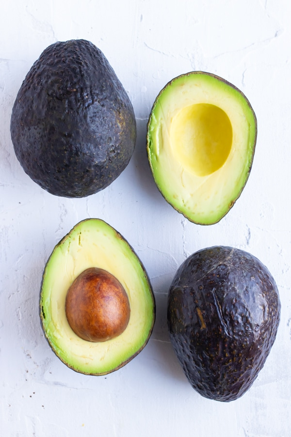 Two whole avocados and two avocado halves to show how to ripen avocados.