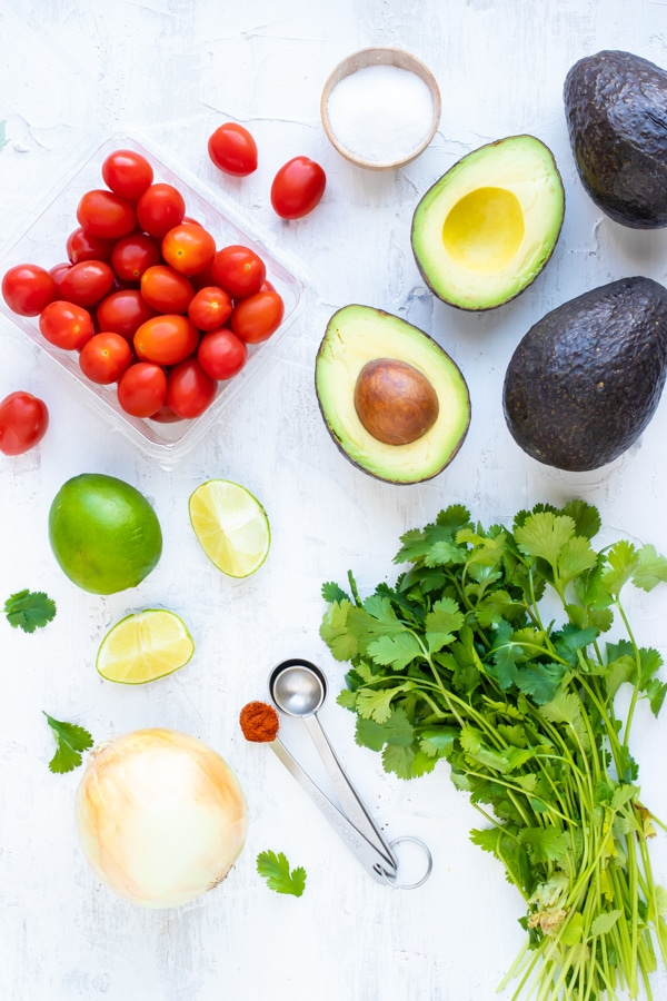 Avocados, tomatoes, onion, lime juice, and cilantro as guacamole ingredients.