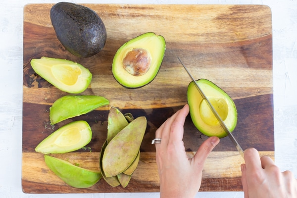 Cut, peeled, pitted, and quartered avocados on a wooden cutting board.