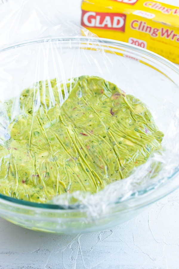Homemade guacamole in a glass bowl with saran wrap on top to keep it from turning brown.