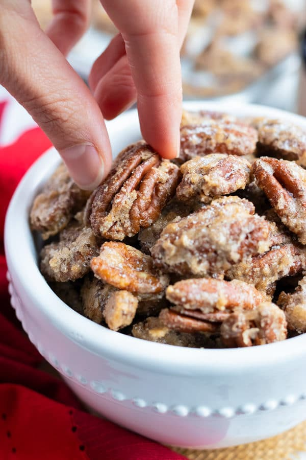 A hand picking up a spiced candied pecan from a snack bowl.
